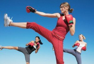 Three women practicing kickboxing, low angle view